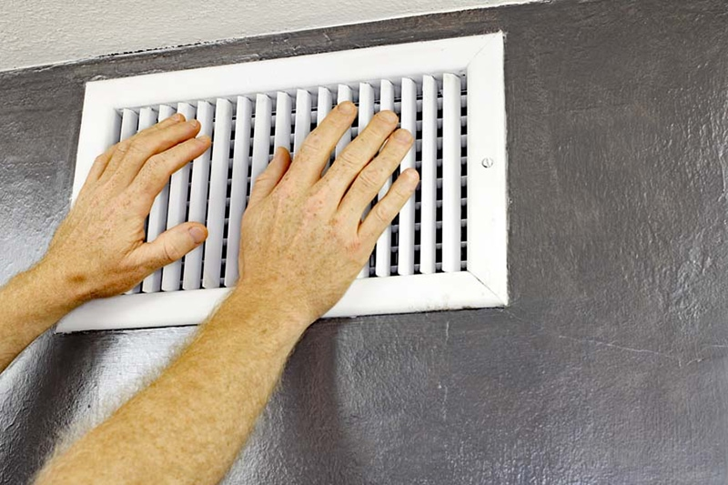 hot air blowing on hands in front of vent